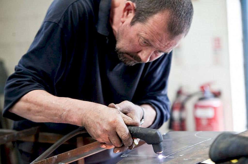 Sculptor Brian Fell working with metal