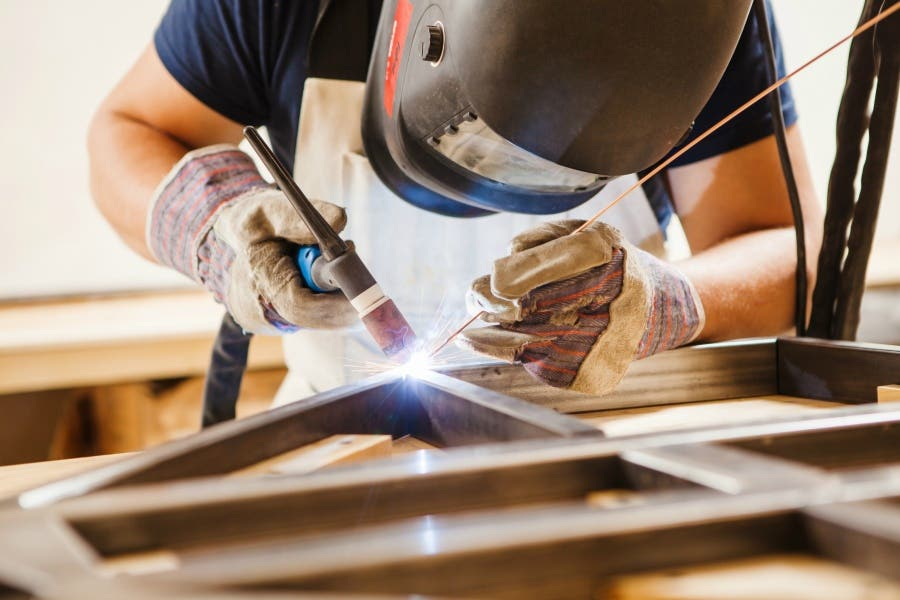 A person welding metal in safety gear